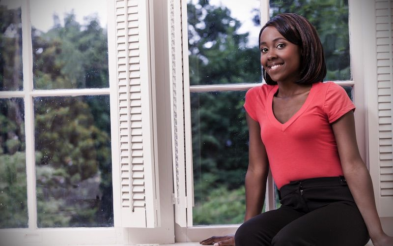 adult student leans on window sill