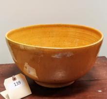 """~12"""" ceramic bowl with an orange glaze."""