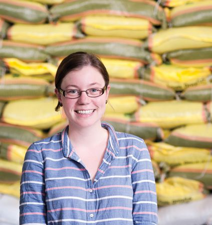photo of Sarah Hylden in front of stack of sacks of food