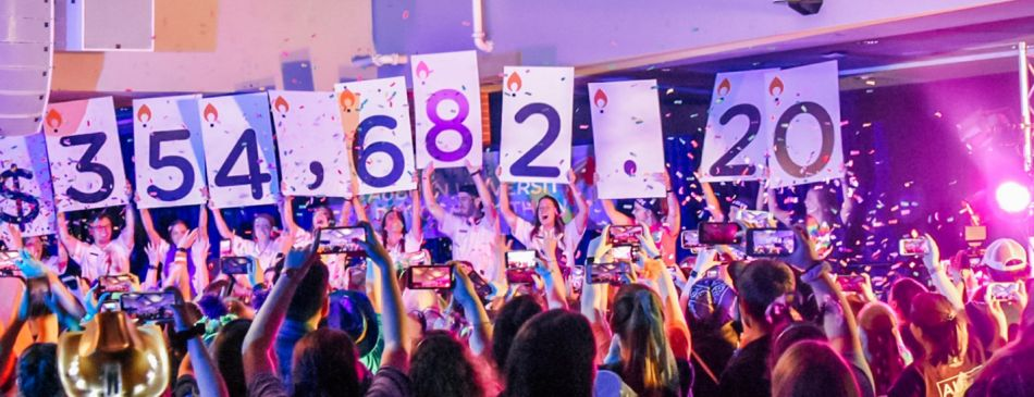 students holding up signs for $354682 dollars