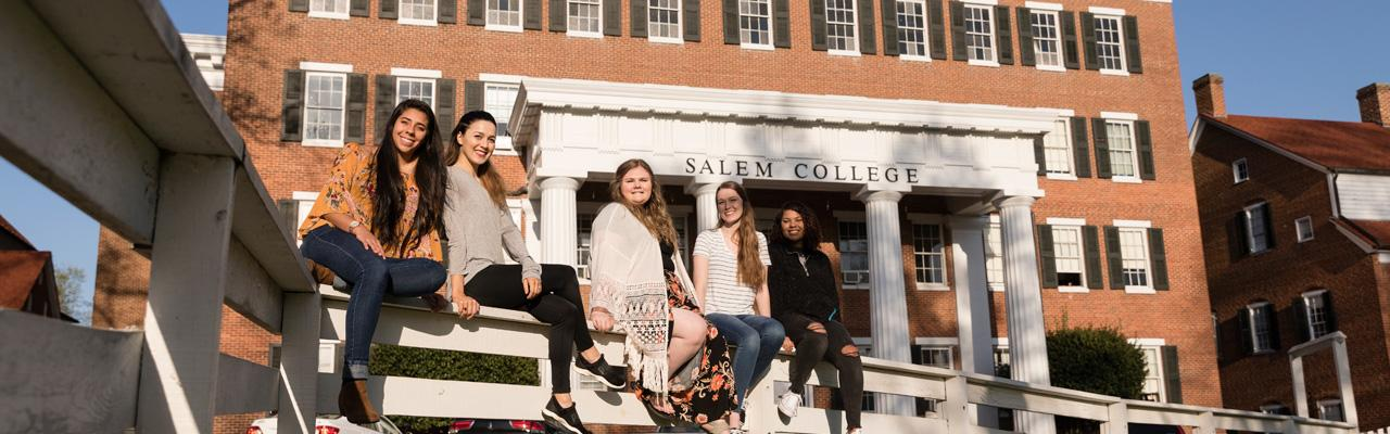 friends sitting on the Salem Square fence in front of main hall