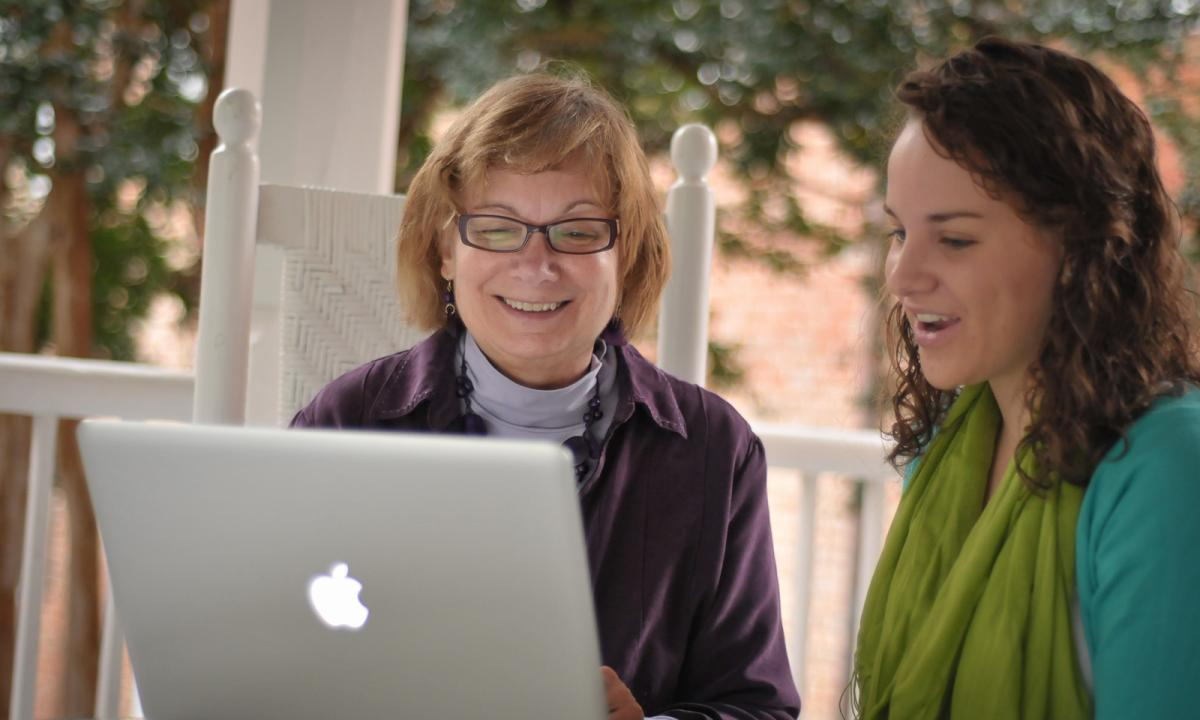 Professor Carol Dykers and student on the back porch of main hall regarding a laptop