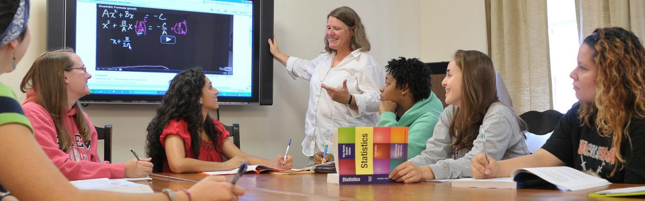 math students at a table with professor viewing plot curves on a HDTV
