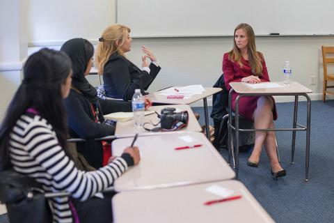 students discussing policy seated in desks at the Center for Women in Business