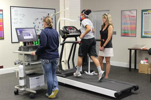 Exercise Science lab; jogger on CO2 sensors, observed by 2 women