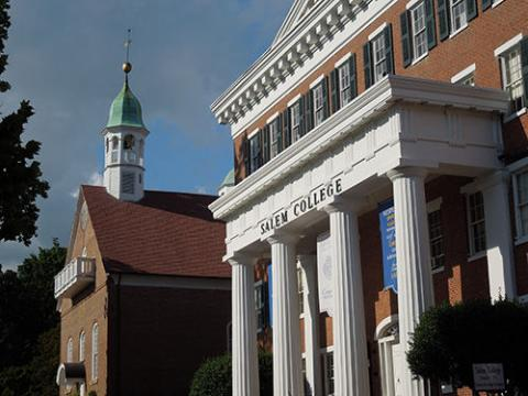 photo of Salem College's Main Hall with Home Moravian Church spire in the background