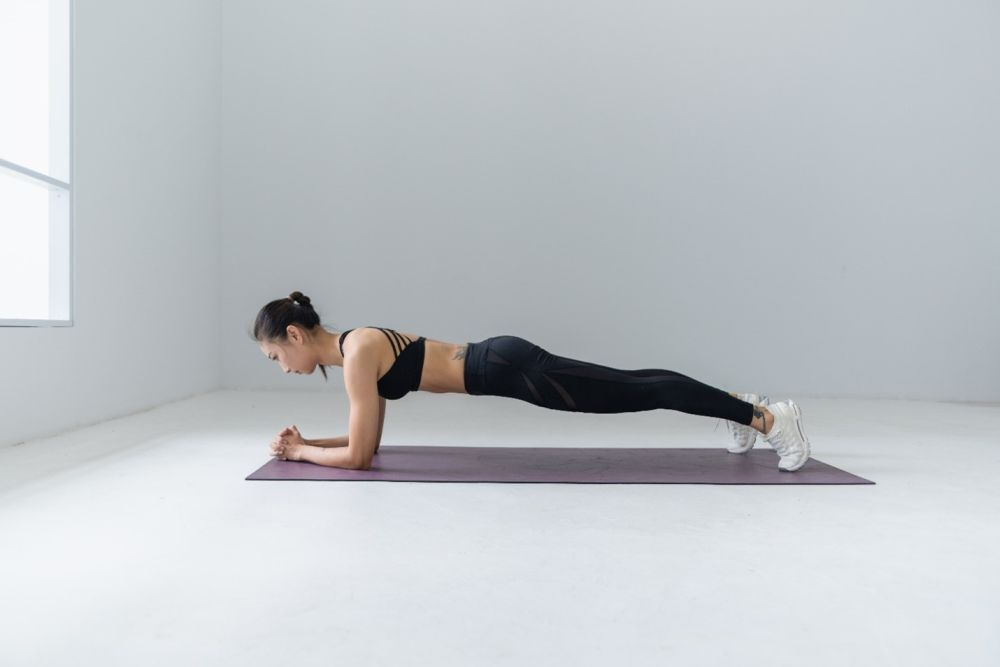 yoga plank position in a white room